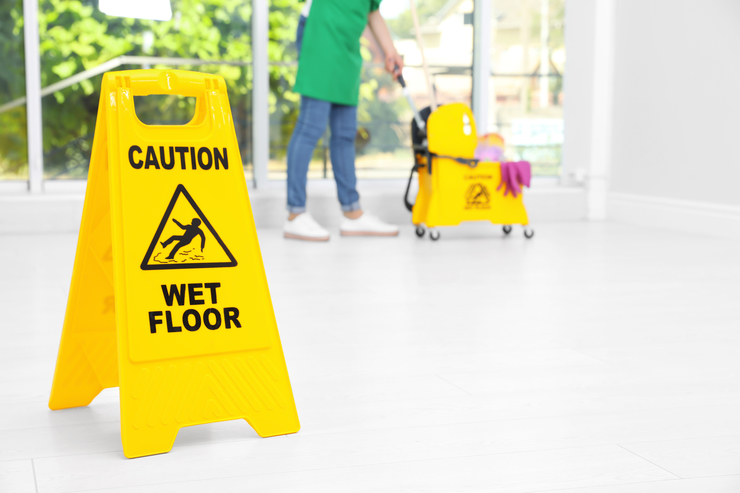 Picture of a CAUTION WET FLOOR sign with our employee in the background cleaning an office floor in Dayton, OH