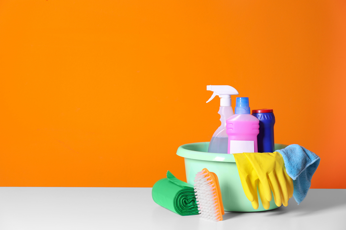 Picture of cleaning products in a bucket with an orange wall. This is product we use in cleaning offices in Dayton, OH